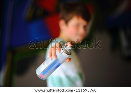 Boy pointing spray can. Focus on spray can with boy out of focus with graffiti in background. - stock photo