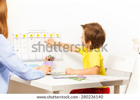 Boy points at activities on calendar learning days - stock photo