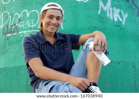 Boy posing in front of graffiti wall - stock photo