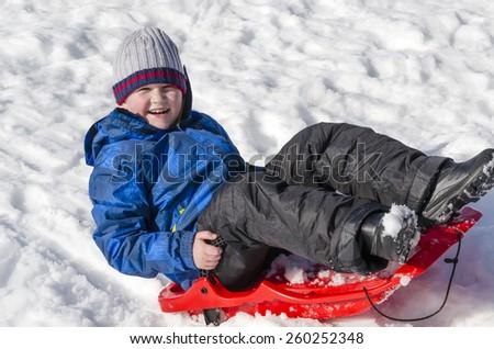Boy posing on a sled. Joyful baby, drop on a sled. - stock photo