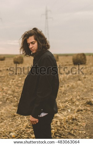 Boy posing on field. Dark. Hipster. Gothic.