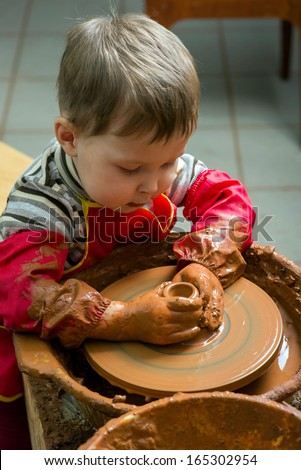 boy potter at work in the studio - stock photo