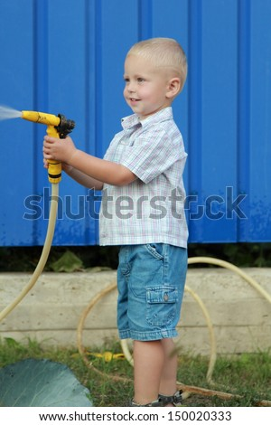 Boy pours water from a hose