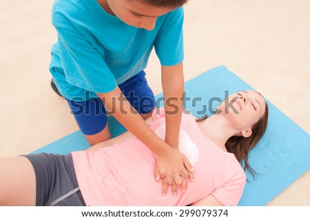 Boy practicing CPR with a woman on the floor. - stock photo