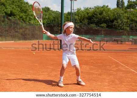 boy practicing tennis forehand - stock photo