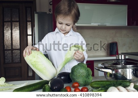 Boy preparing vegetables in the kitchen. The boy cleans a salad. - stock photo