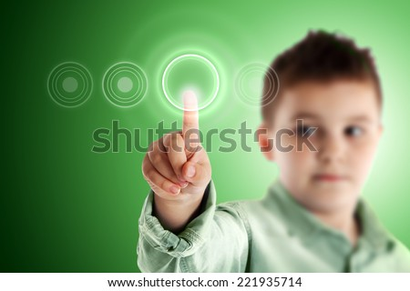 Boy pressing a virtual touch screen. Green background. - stock photo