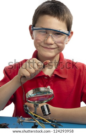 Boy pressing button connected to printed circuit board while wearing safety glasses. - stock photo