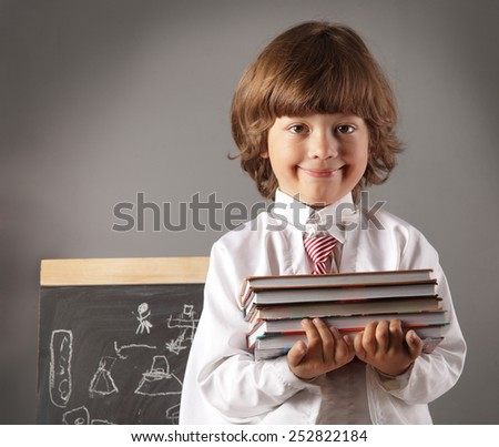 boy primary school students with books at blackboard - stock photo