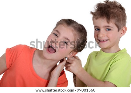 Boy pulling girl's hair - stock photo