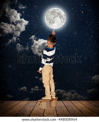 boy pulls out his finger to the moon - stock photo
