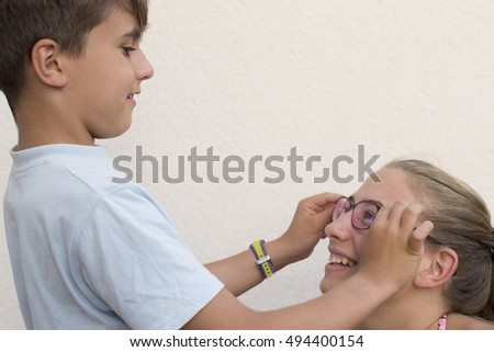 Boy put a glasses to a girl outside