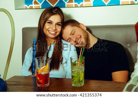 boy put his head on the shoulder of his girlfriend and they are laughing together in cafe. couple relaxing and having fun at the cafe - stock photo