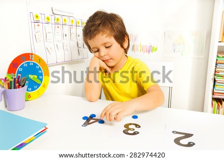 Boy puts learn to count with numbers and values - stock photo