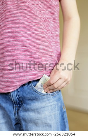 Boy putting cash into jeans pocket - stock photo