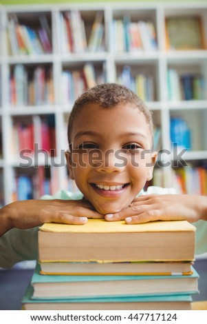 Boy putting his head on books in the library