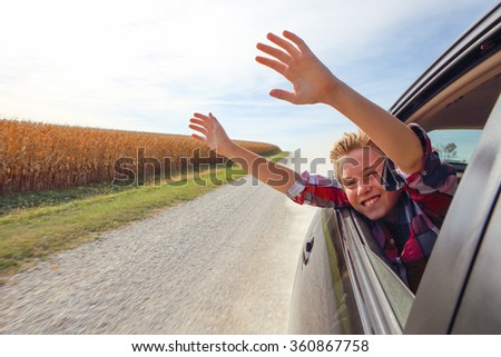 Boy putting his heads and hands out of the car window driving down a country road - stock photo
