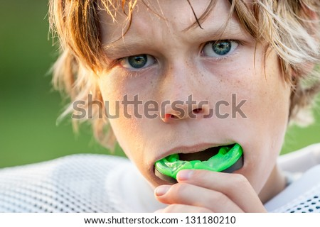 Boy putting in his mouth guard - stock photo