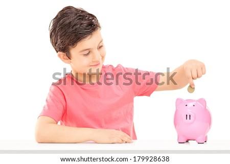 Boy putting money into a piggybank isolated on white background - stock photo