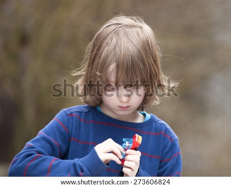 Boy Putting Together his Assembling Toys Outdoors - stock photo