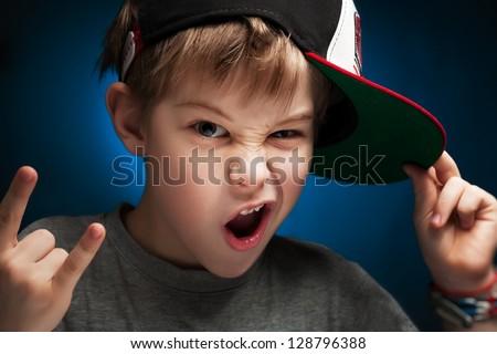 boy rapper poses a face - stock photo