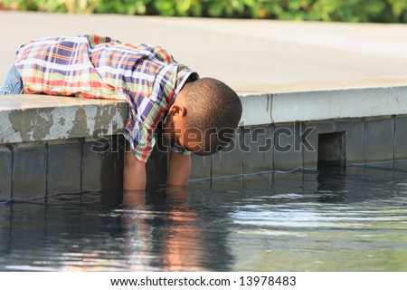Boy Reaching into the Water - stock photo