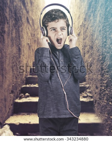 Boy reacts while listening to great music. Cross processed image with shallow depth of field - stock photo