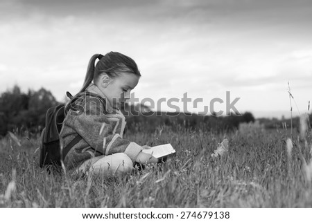 boy reading a book in a meadow - stock photo