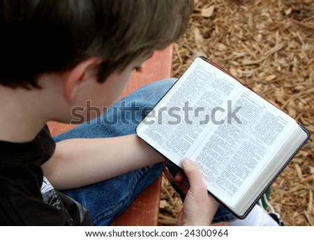 Boy reading Bible at summer youth camp