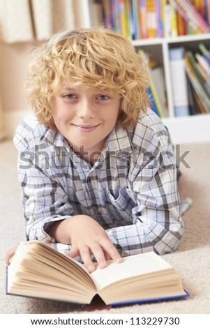 Boy Reading Book In Bedroom - stock photo