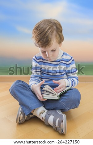 Boy reading book seating on the floor and sunrise background - stock photo