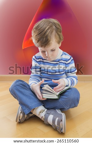 Boy reading book seating on the floor with abstract background - stock photo