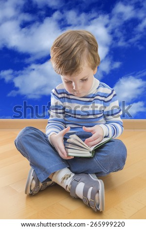 Boy reading book seating on the floor with cloud sky in background - stock photo
