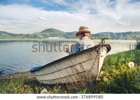 Boy reading in old boat on the lake bank