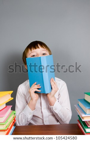 Boy reads a book on a gray background - stock photo
