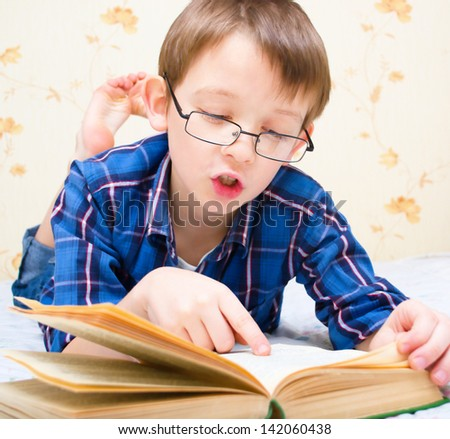 boy reads the book indoors - stock photo