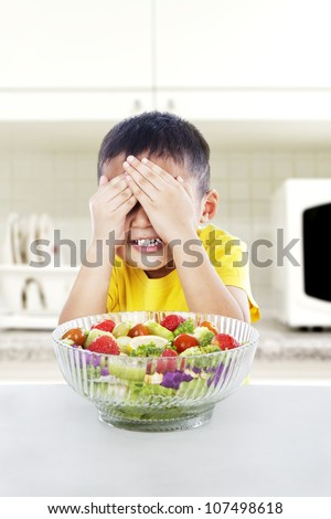 Boy refuses to eat a big portion of salad by cover his eyes. shot in the kitchen - stock photo