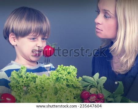 boy refusing to eat tomato - stock photo