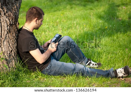 Boy relaxing outdoors and using tablet. Technology and nature concept. - stock photo