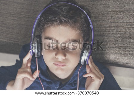 Boy relaxing while listening to music. Cross processed image with shallow depth of field - stock photo