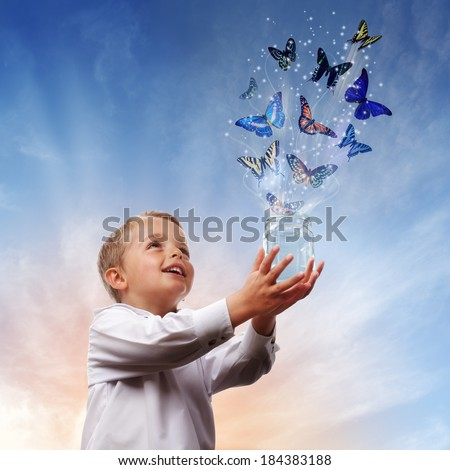 Boy releasing butterflies into the air concept for freedom, peace and spirituality - stock photo