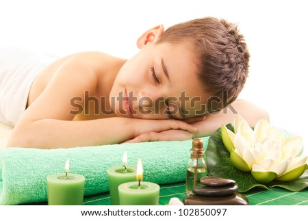 boy rests with spa on the massage table