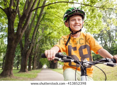 Boy ride a bicycle in city park - stock photo