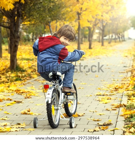 boy riding a bicycle in autumn park - stock photo
