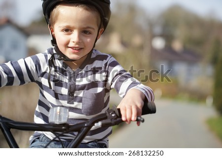 Boy riding a bicycle on a country road concept for healthy lifestyle, exercising and road safety - stock photo