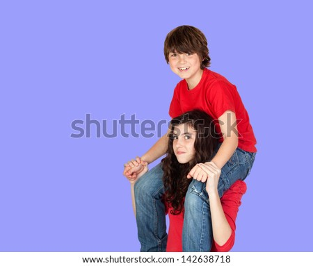 Boy riding on his sister on a blue background - stock photo