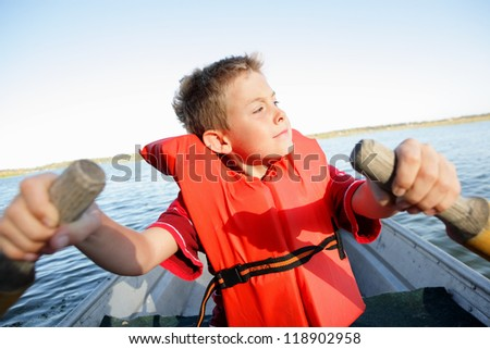 Boy Rowing his own boat - stock photo