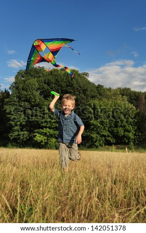 Boy running across the field with kite flying over his head - stock photo