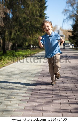 Boy running along road in park, outdoor - stock photo