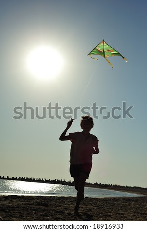 Boy running and flying a kite